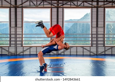 The concept of fair wrestling. Two greco-roman  wrestlers in red and blue uniform making a suplex wrestling  on a wrestling carpet in the gym.The concept of male wrestling and resistance