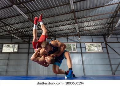 Das Konzept des fairen Ringes. Zwei greco-roman Ringkämpfer in rot und blau-einheitlichem Ringkampf   im Fitnessraum auf einem Ringelteppich.