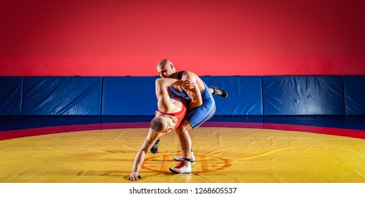 The concept of fair wrestling. Two young men in blue and red wrestling tights are wrestlng and making a hip throw on a yellow wrestling carpet in the gym