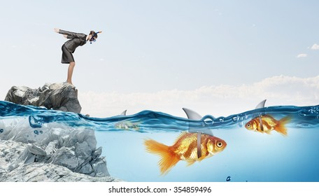 Concept of fake threat when businesswoman jump in water with shark appear to be goldfish