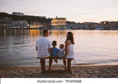 concept family beach vacation. Family of four people mom, dad and brothers children boys sitting on the river bank with their backs on a wooden bench at sunset in summer.