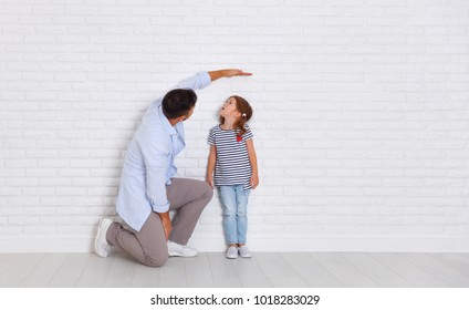 concept of the family. the father measures growth of child to a daughter near an empty wall