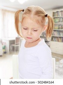 The concept of family happiness,and preschool education of the child , against a child's room with bookshelves.Distressed small, blonde girl with white t-shirts without a pattern.