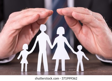 Concept of family insurance with hands protecting a family