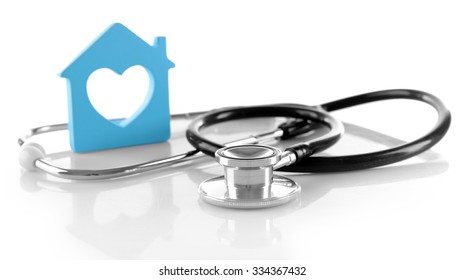 Concept of family medicine - blue plastic house with heart shaped window and stethoscope isolated on white background