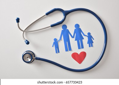 Concept of family medicine with ostetoscope and paper cut of family and heart on a white table. Top view. Horizontal composition.