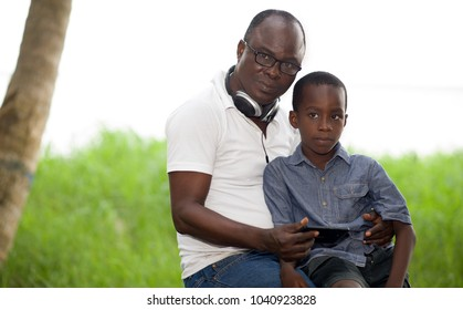 concept of family, paternity and people - father and son sitting in the garden and using a mobile phone