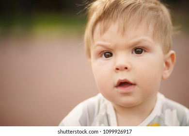 Concept: family values. Close-up portrait of adorable innocent funny brown-eyed baby playing at outdoor playground with serious face.
