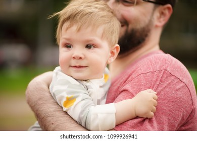 Concept: family values. Close-up portrait of adorable innocent funny brown-eyed baby smiling with his hipster father.
