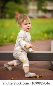 Concept: family values. Portrait of adorable innocent funny brown-eyed baby playing at outdoor playground with serious face.