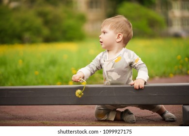 Concept: family values. Portrait of adorable innocent funny brown-eyed baby playing at outdoor playground.