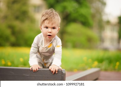 Concept: family values. Portrait of adorable innocent funny brown-eyed baby play at outdoor playground with serious face.