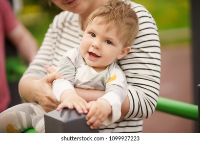 Concept: family values. Portrait of adorable innocent funny brown-eyed baby smiling and playing with his mother.