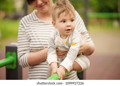 Concept: family values. Portrait of adorable innocent funny brown-eyed baby smiling and playing with his mom.