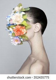 Concept fashion studio portrait of nude elegant lady with flower on her face
