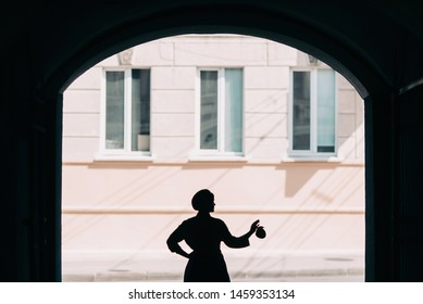 The concept of fashionable summer, blue and green colors. Stylish young woman in blue beret and skirt with a green shirt is standing on the street in the arched doorway silhouette close view