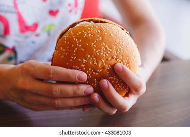 The concept of fast food. Tasty unhealthy Burger sandwich in hands, getting ready to eat in the restaurant on a wooden table