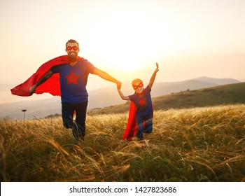 concept of father's day. dad and child daughter in hero superhero costume at sunset in nature