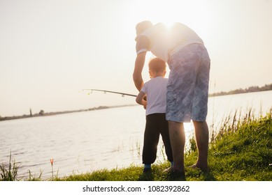concept of father's day. Father and son fishing together