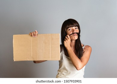 The concept of feminism and women's rights. A woman holds a cardboard banner in her hands, imitating a man's mustache on her face with her hair. Copy space