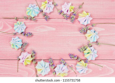 concept of festive background, on pink wooden boards lined with colorful meringues and blue flowers