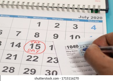 Concept of filling tax form before deadline july 15th with july 15th marked as tax day on calender as background.