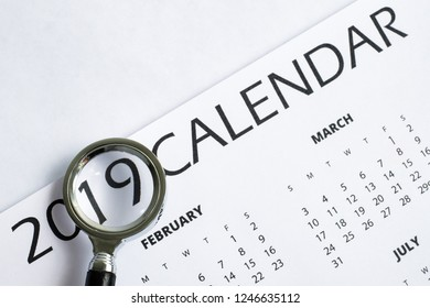 The concept of financial audit in 2019. Printed calendar under a magnifying glass.