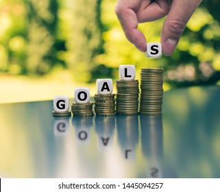 "Concept of financial goals. Dice placed on increasing high stacks of coins form the word ""GOALS""."