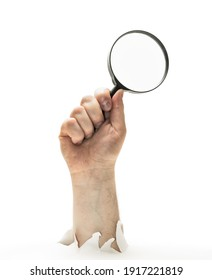 Concept of finding. Man's hand with magnifying glass stick out of hole in paper. Isolated on white.