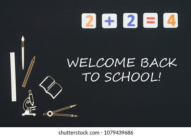 Concept first class school, text welcome back to school with wooden miniatures school supplies and elementary numbers on black background