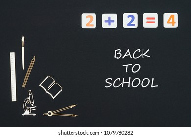 Concept first class school, text back to school with wooden miniatures school supplies and elementary numbers on black background