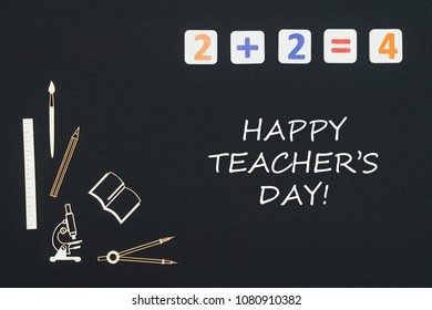 Concept first class school, text happy teacher's day with wooden miniatures school supplies and elementary numbers on black background