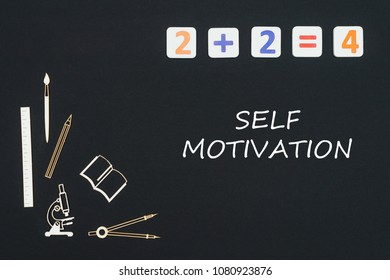 Concept first class school, text self motivation with wooden miniatures school supplies and elementary numbers on black background