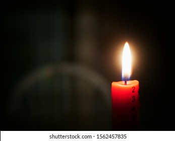 Concept of first day of advent shown by red advent candle with numbered advent days down the side, lit with flame in dark room