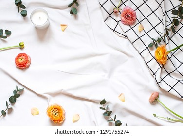 Concept flat lay with flowers and leaves on the white blanket. Valentines day, Mothers day or Womens day top view frame. Copy space