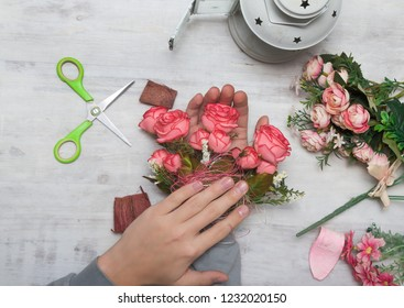 Concept of floristry on a white vintage background, drawing up bouquets of flowers in the store