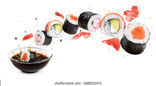 Concept of flying sushi with ingredients isolated on white background. Piece of sushi drops in a bowl with soy sauce. With clipping path.