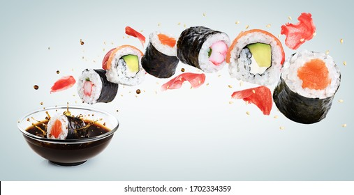 Concept of flying sushi with ingredients on light background. Piece of sushi drops in a bowl with soy sauce. With clipping path.
