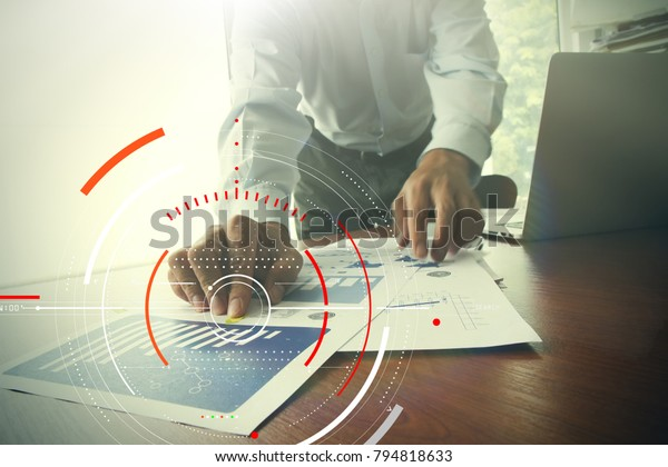 Concept of focus on target with digital diagram,graph interfaces,virtual UI screen,connections network.Hipster finance analist working at trendy office