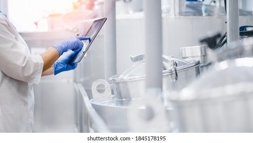 Concept food industry banner. Factory worker inspecting production line tanker in of dairy factory with computer tablet.