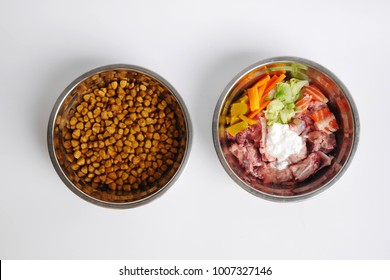 Concept of food for pets. Barf, Natural and dry food in metal bowls isolated on white background