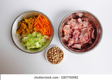 Concept of food for pets. Barf, raw food for dog in metal bowls isolated on white background with yeast