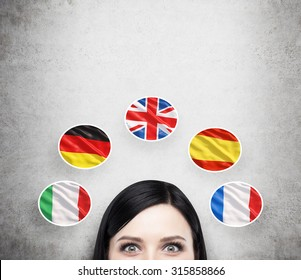 A concept of foreign language studying process. A foreseen of the brunette girl surrounded by icons of european flags. Concrete background.