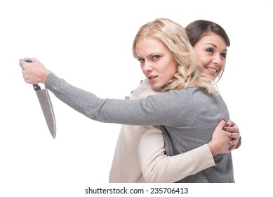 The concept of fraud. Two women embrace. One of them is holding a knife behind back.