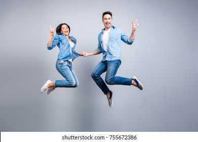 Concept of freedom, carelessness, good mood and enjoying life. Totally glad and happy lovers in jeans denim casual clothes are jumping up and showing v-sign, they are isolated on grey background.