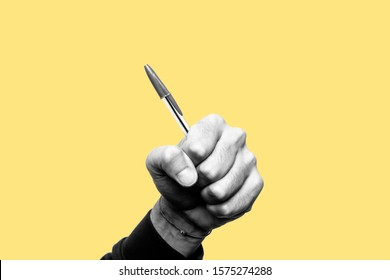 Concept of freedom of speech and information, stop censorship. Hand holding a pen like a weapon. Defend the freedom of Journalism. Black and white subject with a yellow background