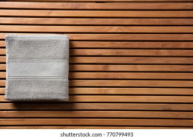 Concept for freshness, hygiene, shower, bath, Turkish bath, spa or body care concept with soft grey cotton towel over beautiful wooden board, beauty spa copy space wallpaper, top view