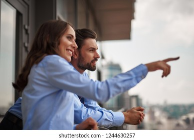 Concept of friendly communication between coworkers. Close up portrait of young smiling woman showing something to man from office balcony while have work break