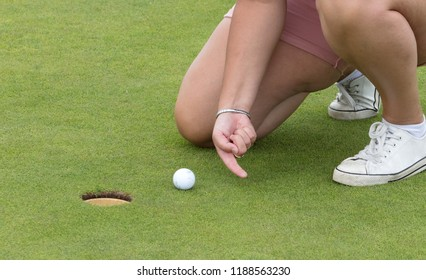 Concept of fun; Playing golf with a finger - Cheating