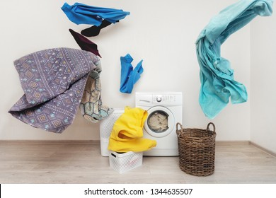 Concept of funky and easy laundry process. White washing machine standing inside flat with bright interior near flying multicolored clothes